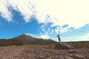 Mujer de pie abrindo brazos frente a montaña
