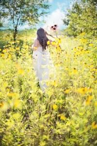 Mujer caminando de espalda en camino de flores amarillas