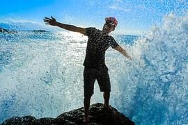 Hombre feliz en contacto con agua del mar