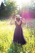 Mujer de espalda con sombrero, en un campo, rayos del sol