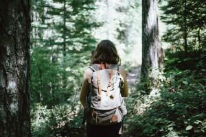 Mujer con mochila de espalda en un bosque, perdida