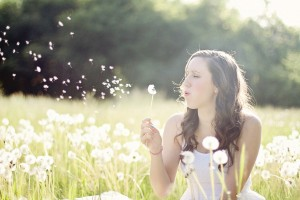 Mujer soplando una flor en el campo